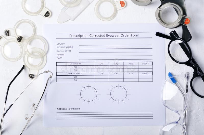Blank prescription for corrective eyeglasses, different types of pair of glasses, optometrist`s  professional tools on the white t royalty free stock photography