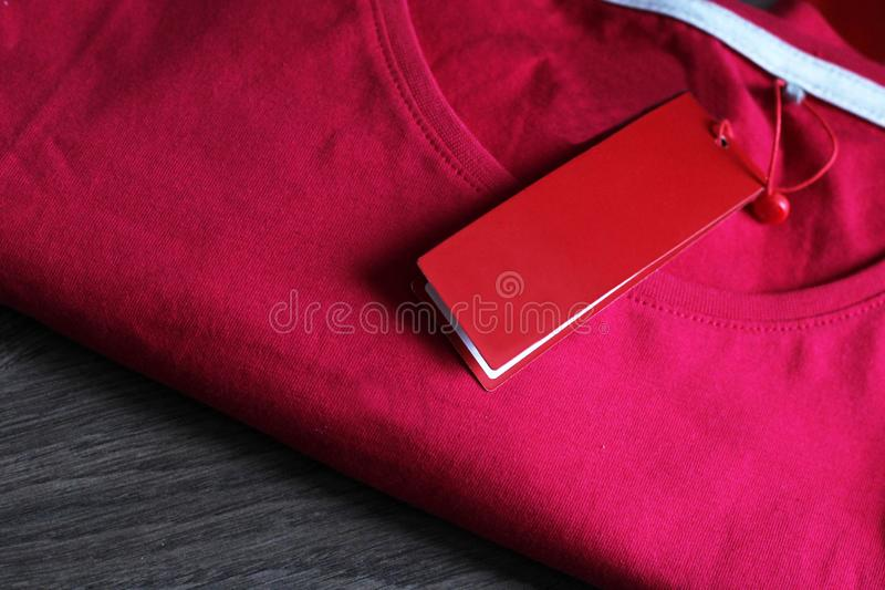 Blank price tag hang over t-shirt, pink color. Ed stock image