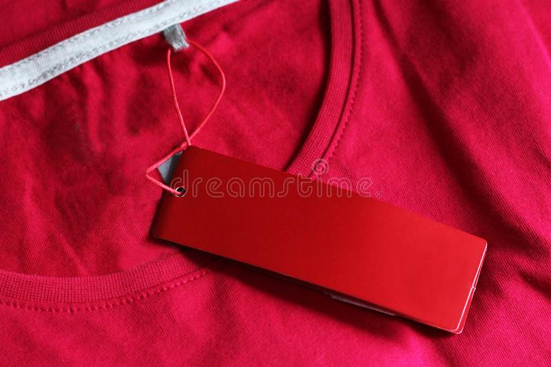 Blank price tag hang over t-shirt, pink color. Ed royalty free stock image