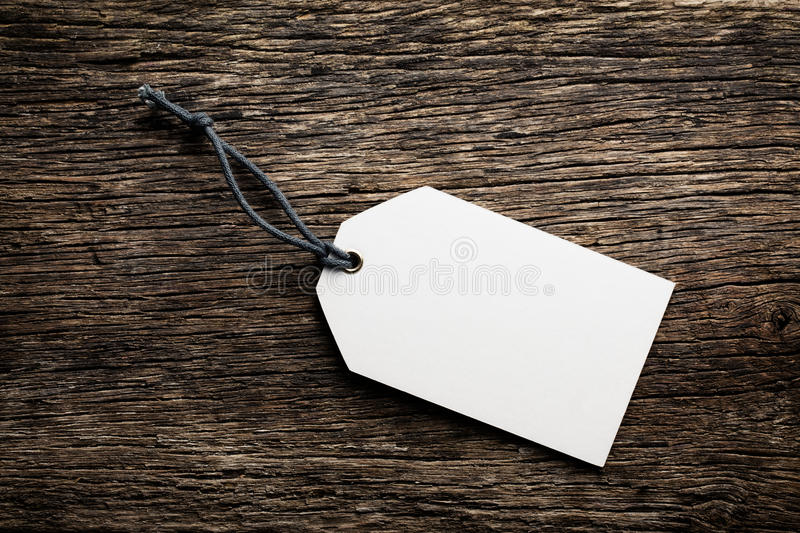 Blank price tag label on wooden background. The blank price tag label on wooden background stock image