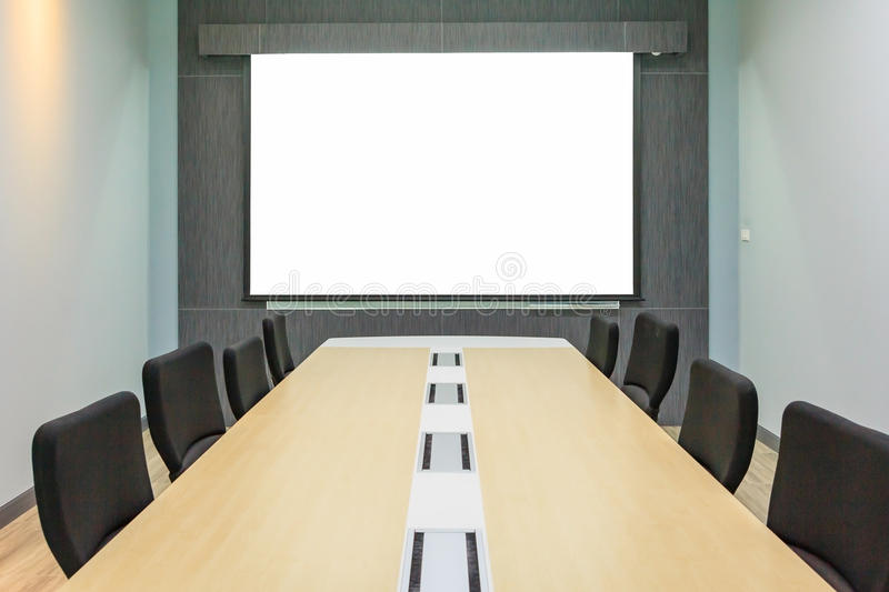 Blank projection screen in meeting room with conference table stock images
