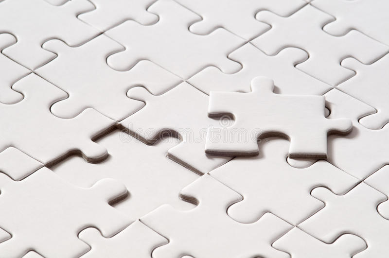 Blank Puzzle. Photo of a blank puzzle with one piece missing. All the puzzle parts are white and blank stock photo