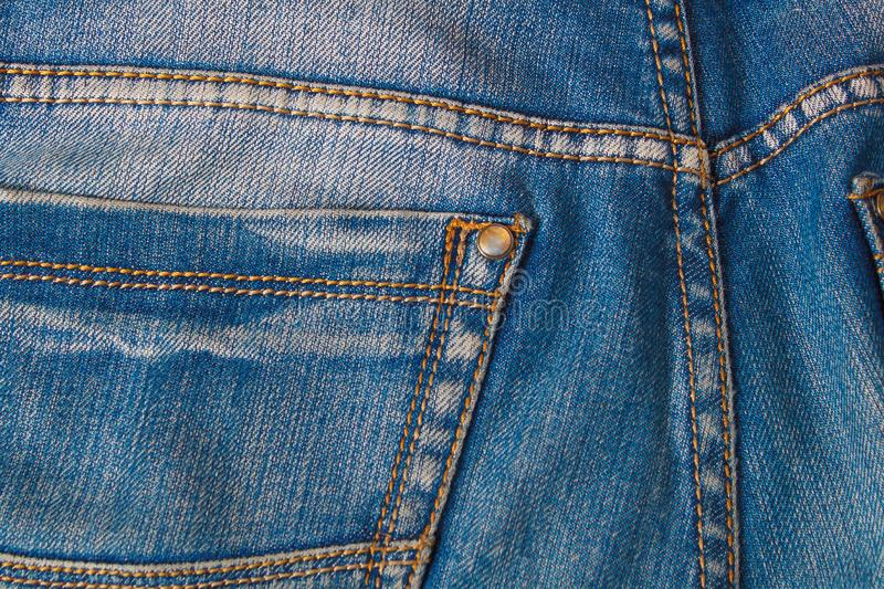 Blank real leather jeans label sewed on old worn blue jeans stock photo