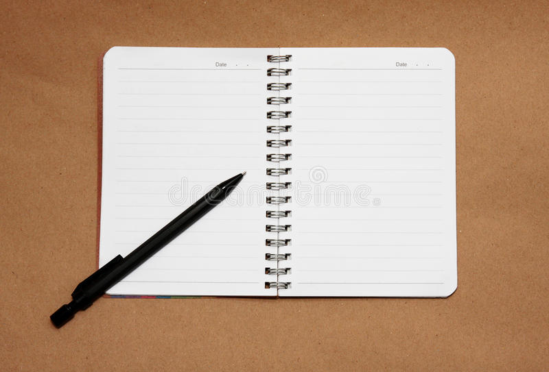 Blank reporters notebook and pencil on a brown pap