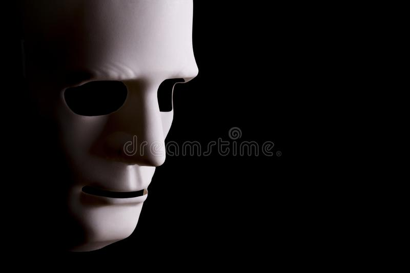 Blank robotic face on black background. Blank robotic face mask looking sideways with a black background and copy space stock photos