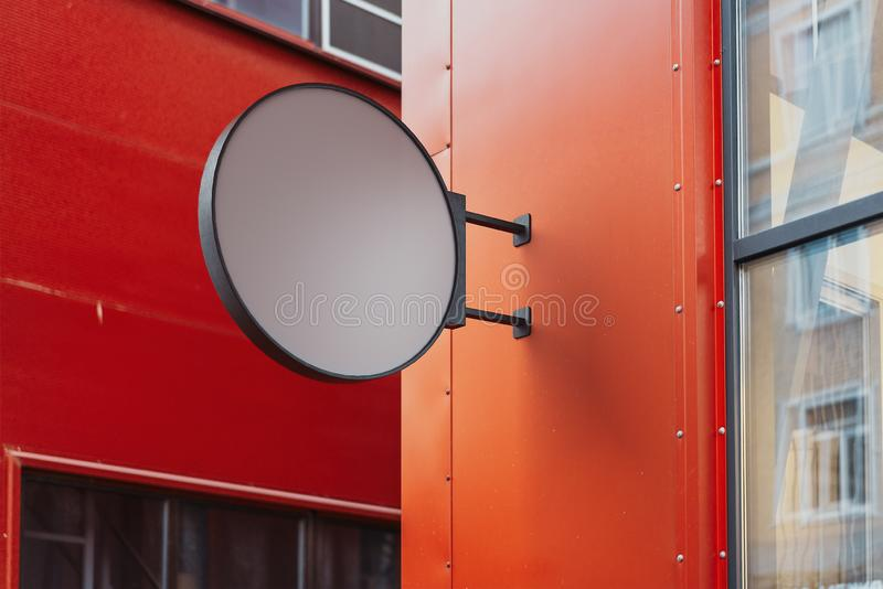 Blank round store signboard. Empty shop lightbox on the red wall. 3d rendering. royalty free stock photo
