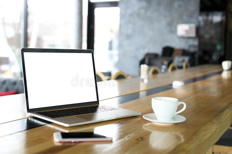 Blank screen laptop and cell phone with cup of coffee on wooden table of hipster cafe bar, big windows. Smartphone gadget & notebo. Ok computer. Freelance work royalty free stock photography