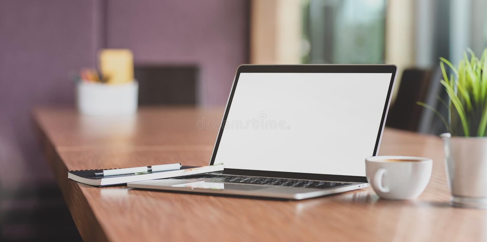 Blank screen laptop computer and a cup of coffee in modern meeting room royalty free stock photo