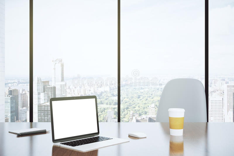 Blank screen of laptop and paper cup on the table with white chair and city view from big window, mock up royalty free stock photography