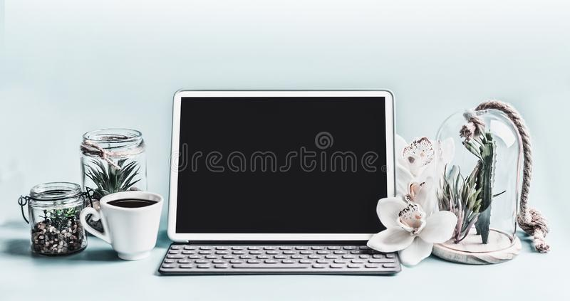 Blank screen modern laptop computer with succulent plants in glasses and orchid flowers on table. Home female business office stock photography