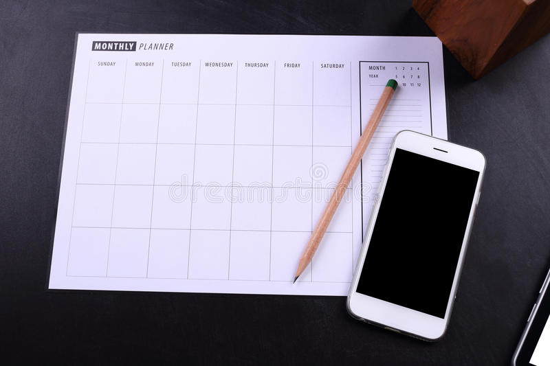 Blank screen smartphone and planner schedule. On black wooden background royalty free stock photos