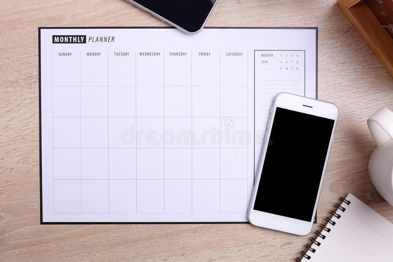 Blank screen smartphone planner schedule and office supplies on. Blank screen white smartphone planner schedule and office supplies on wooden background royalty free stock photography