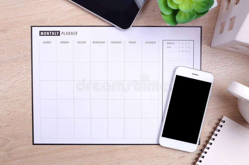 Blank screen smartphone planner schedule and office supplies on. A wooden background stock image
