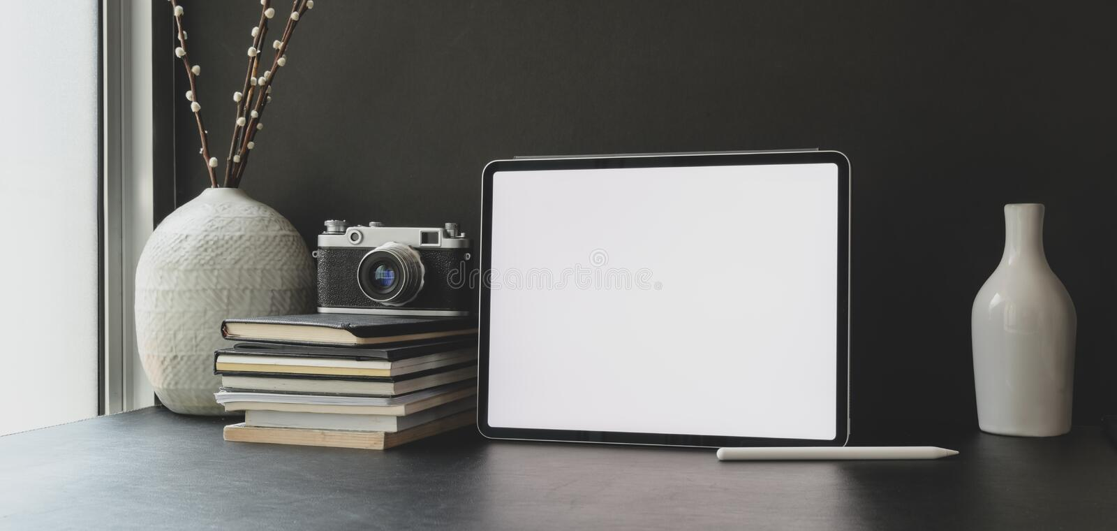 Blank screen tablet in dark trendy workspace with office supplies and ceramic vases decoration. S royalty free stock images