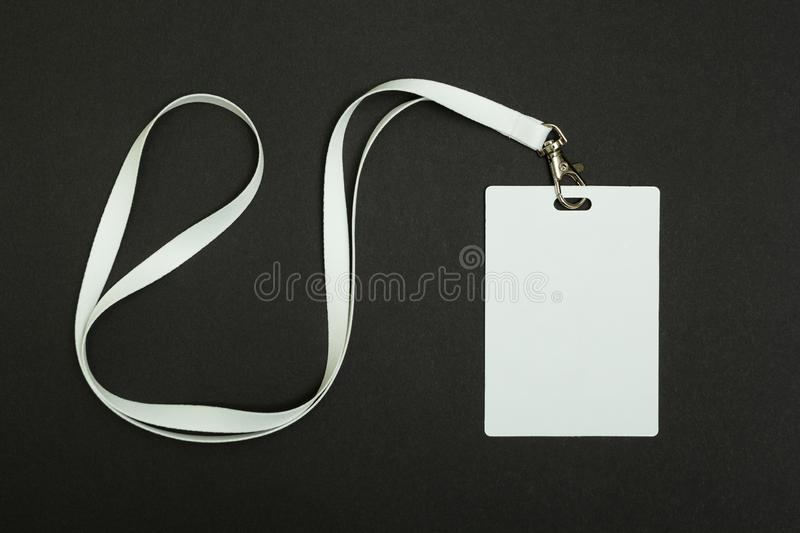 Blank Security Tag with White Neck Band Isolated on Black Background royalty free stock images