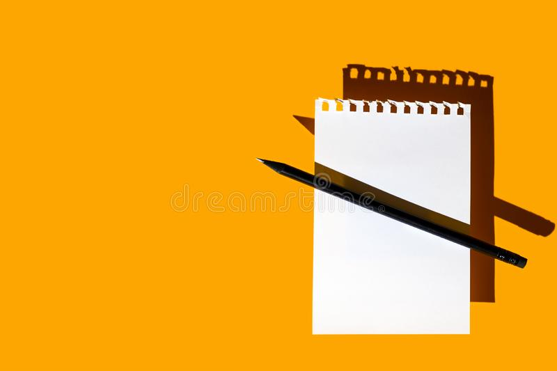 A blank sheet of Notepad, black pencil and hard shadows on bright yellow background stock photos