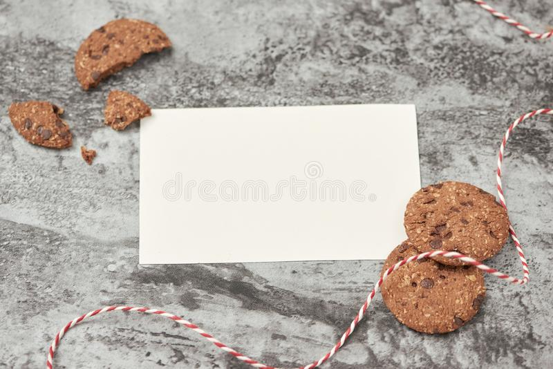 Blank sheet of paper with chocolate cookies on stone table royalty free stock photos