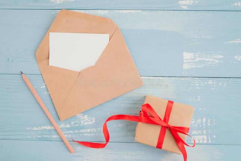 Blank sheet paper for greeting text and gift box. Top view. Flat royalty free stock photo