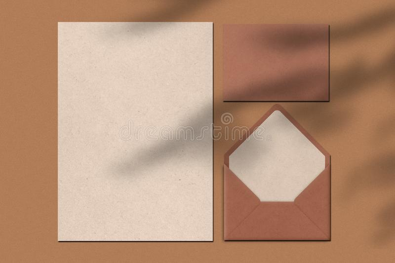 Blank sheet of paper and letter against brown background. Envelope. Writing notes concept. Top view. Horiontal shot. Empty space royalty free stock photography