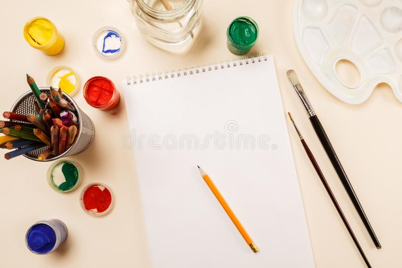 Blank sheet of paper, pencils, paint jars on a table, top view stock photography
