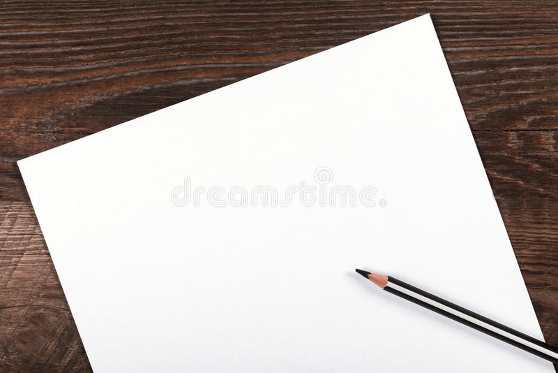 Blank sheet of paper. A blank sheet of paper on a wooden background royalty free stock photo