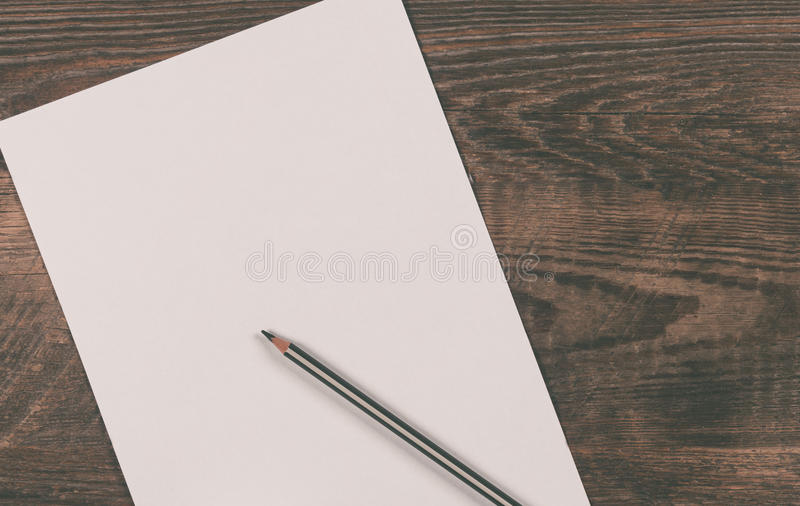 Blank sheet of paper. A blank sheet of paper on a wooden background royalty free stock images