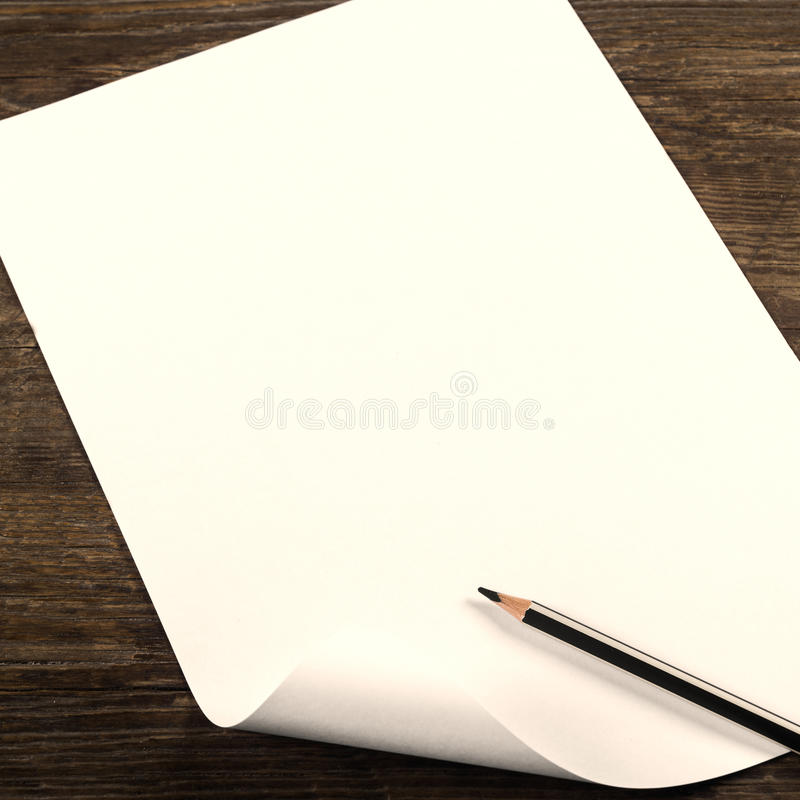 Blank sheet of paper. A blank sheet of paper on a wooden background royalty free stock photos