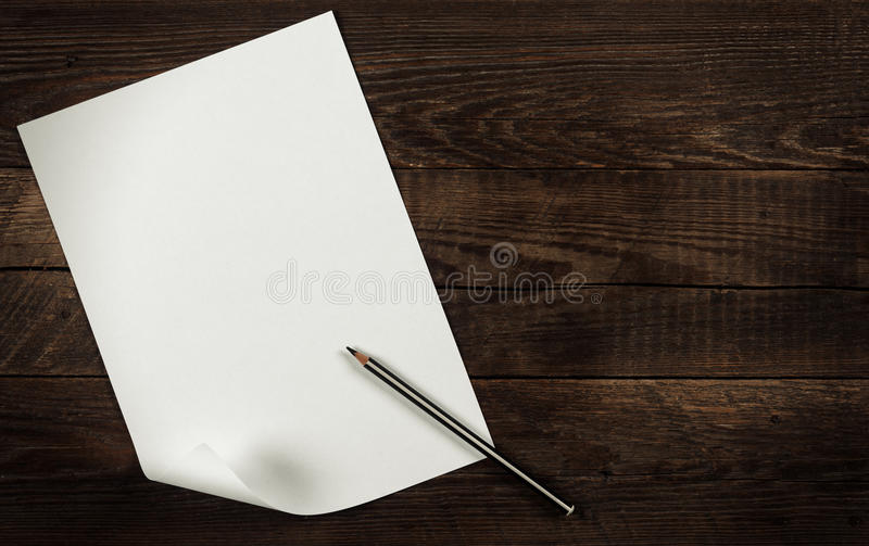 Blank sheet of paper. A blank sheet of paper on a wooden background stock photo
