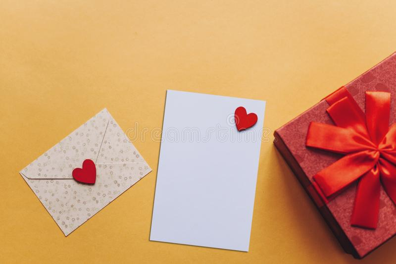Blank sheet with red heart for text or write. Near an envelope with a heart to send and a box with a gift. stock photo