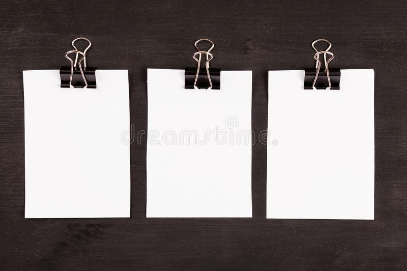 Blank sheets of white paper with paper clip on a black background royalty free stock image