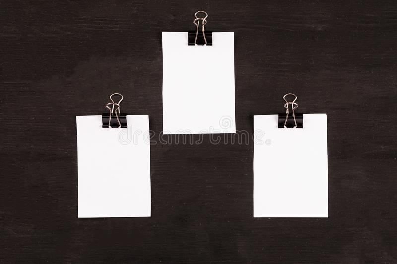 Blank sheets of white paper with paper clip on a black background royalty free stock photos