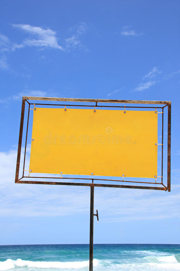 Blank sign on the beach. Blank sign with yellow vinil on a rusty metal frame for advertising items for sale or for rent on the beach ina summer day stock images