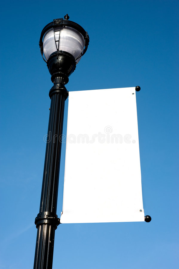 Blank Sign on Lamp-post. A blank white sign on a lamp-post in front of a blue sky, add your own copy or graphic, copy space. Includes clipping path for sign area royalty free stock photo