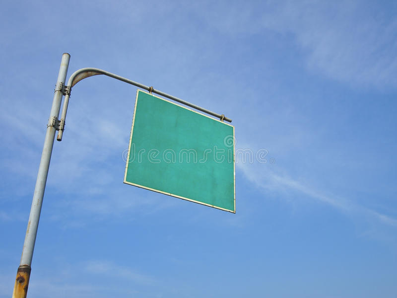Blank signboard. Blank traffic signboard hang on high pole in sunny day royalty free stock photo