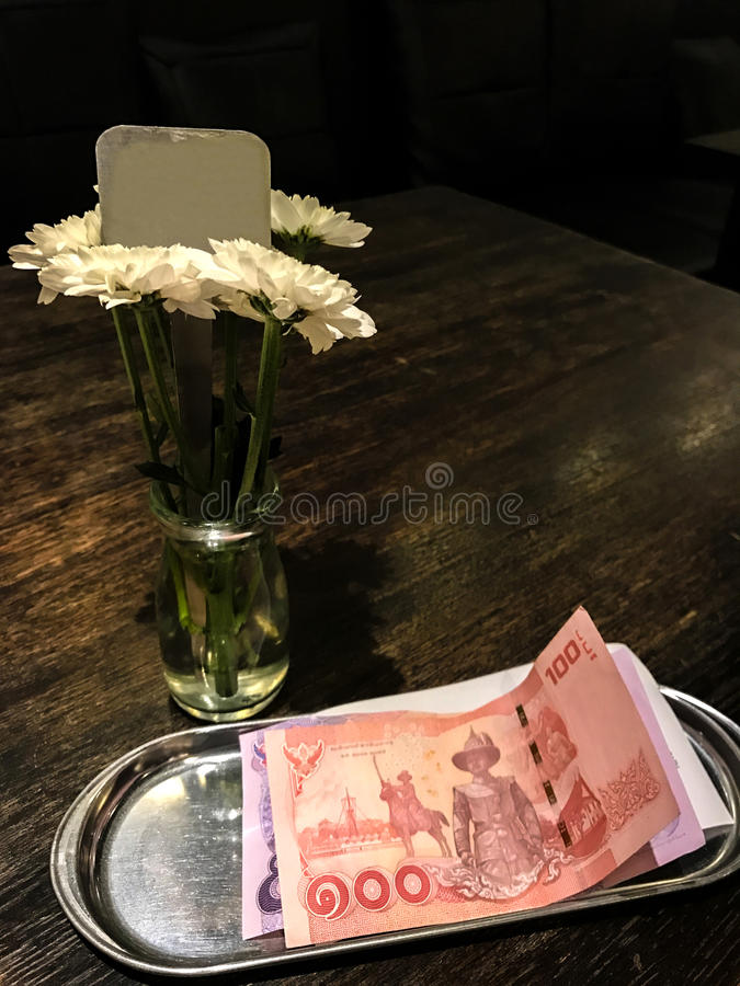 Blank signpost on flower glass vase and Thai Bank Notes one hundred Baht and five hundred Baht bank notes on silver tray royalty free stock images