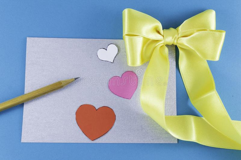 A blank silver letter with a big yellow bow wooden pencil and small pink white red hearts on a blue background. Letter or invitation Minimalist concept Copy stock images