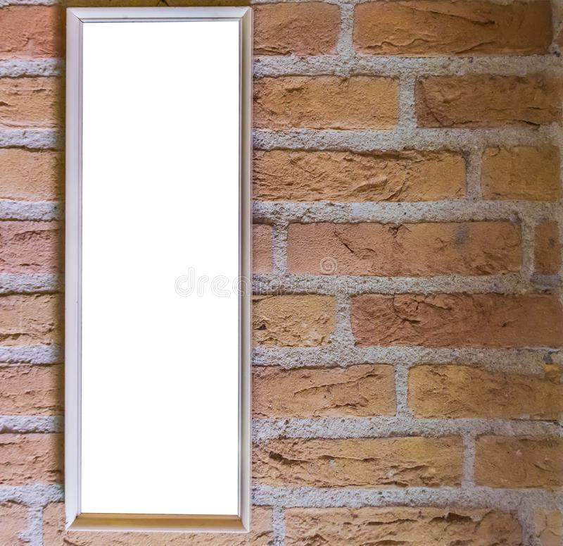 Blank small long white rectangular shaped picture frame hanging on a brick wall background stock photos