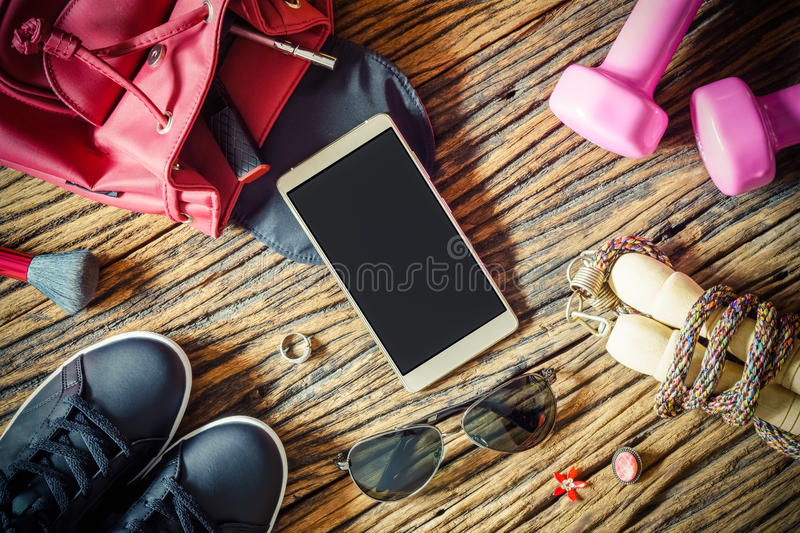 Blank Smartphone and Sport equipments, Fitness, healthy and active lifestyles Concept, sport shoes, dumbbells and blank notebook. On wooden background. copy royalty free stock images