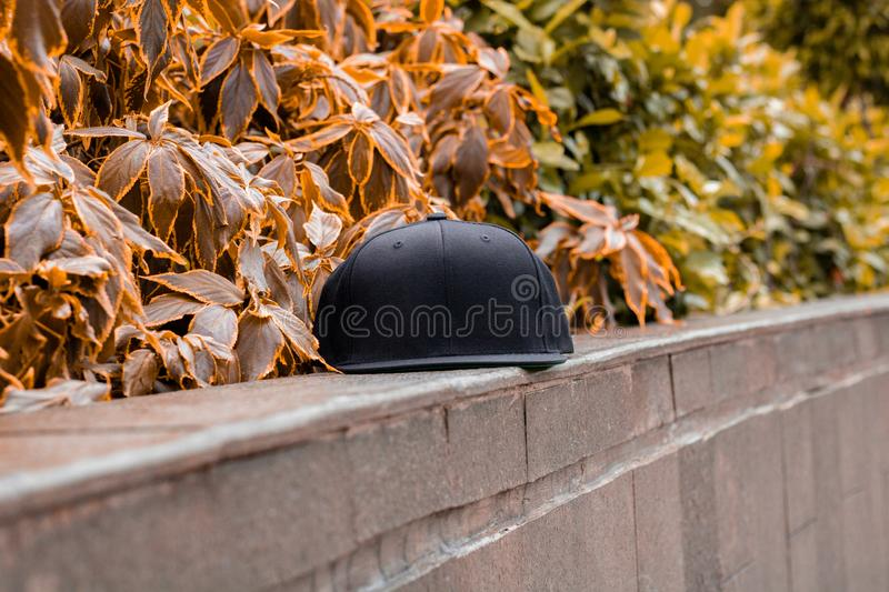 Blank black snapback hat cap flat visor for mockup. Blank snapback hat cap flat visor with black color in outdoor, ready for your mock up design or presentation stock photos