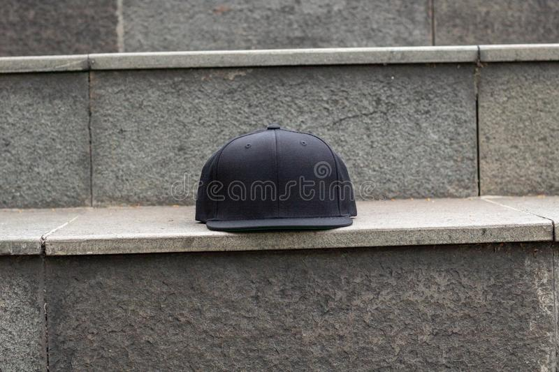 Blank black snapback hat cap flat visor for mockup. Blank snapback hat cap flat visor with black color in outdoor, ready for your mock up design or presentation stock image