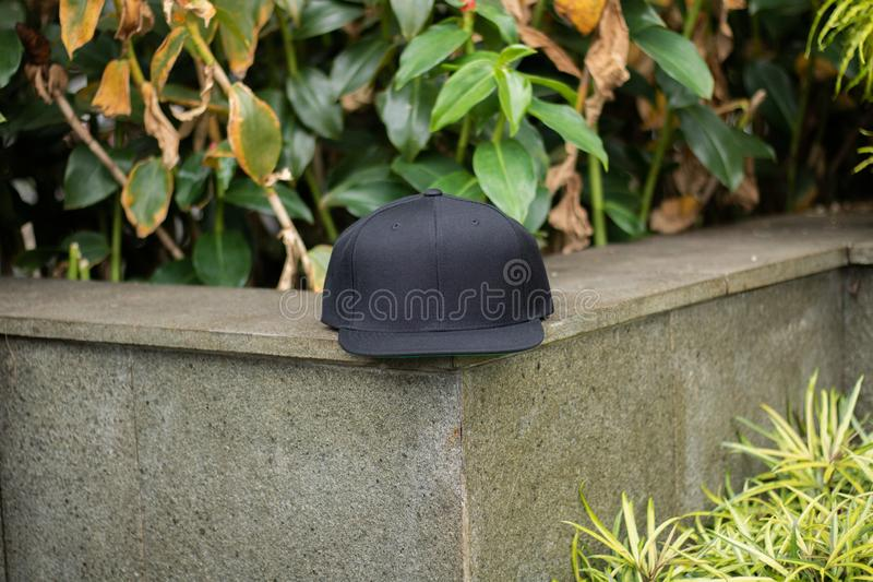 Blank black snapback hat cap flat visor for mockup. Blank snapback hat cap flat visor with black color in outdoor, ready for your mock up design or presentation royalty free stock image