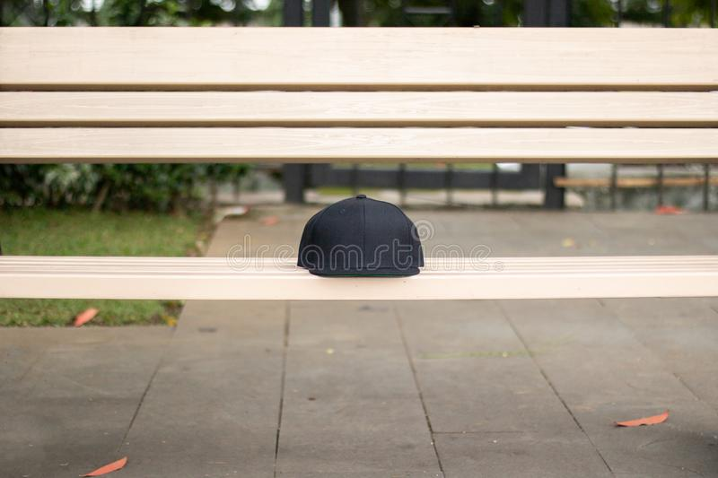 Blank black snapback hat cap flat visor for mockup. Blank snapback hat cap flat visor with black color in outdoor, ready for your mock up design or presentation royalty free stock photo