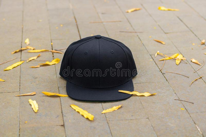 Blank black snapback hat cap flat visor with black color. Blank snapback hat cap flat visor with black color in outdoor, ready for your mock up design or stock image