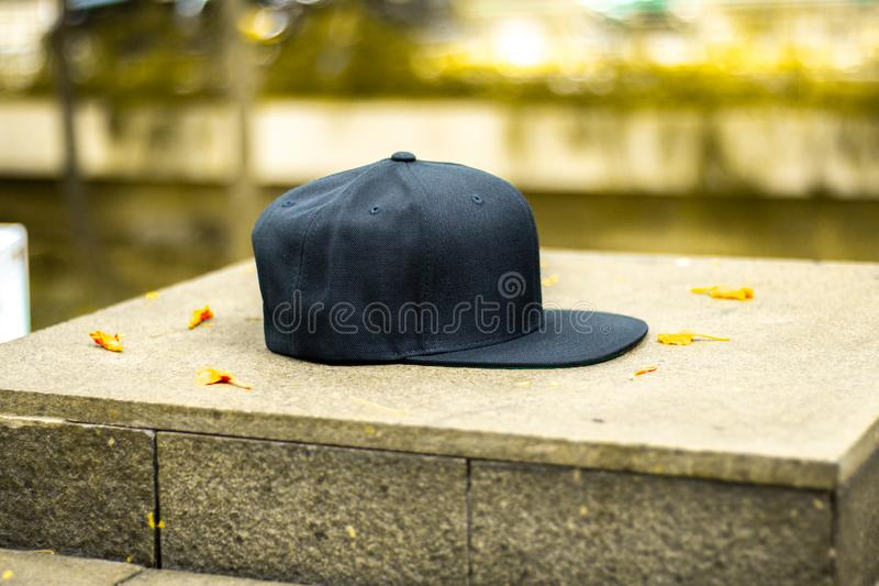 Blank black snapback hat cap flat visor with black color. Blank snapback hat cap flat visor with black color in outdoor, ready for your mock up design or royalty free stock image