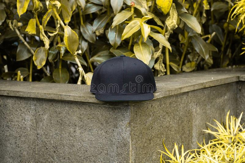 Blank black snapback hat cap flat visor for mockup. Blank snapback hat cap flat visor with black color in outdoor, ready for your mock up design or presentation stock photography