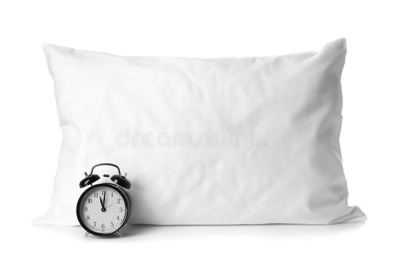 Blank soft pillow and alarm clock. On white background stock photo