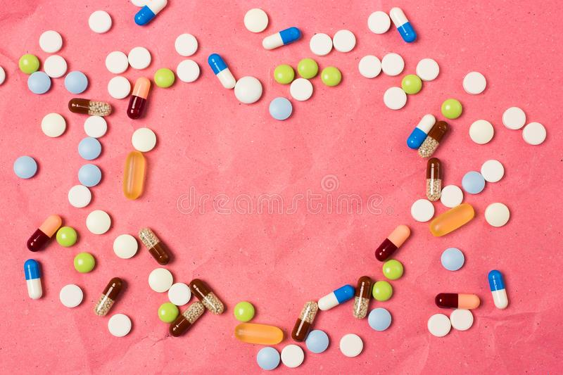 Blank space heart shaped frame for text with color pills, pills and capsules stock photos