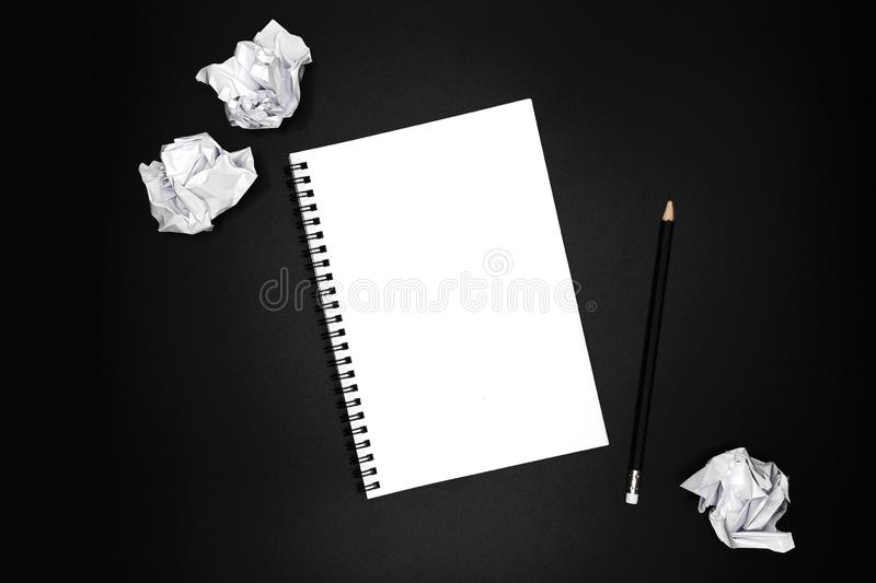 Blank spiral notebook with black pencil and crumpled papers on black background. Business concept stock photos