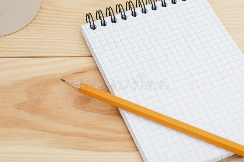 Blank spiral notebook with pencil laying on wooden desk. Modern designer home desk table with blank notepad page. Top view, flat l royalty free stock photos