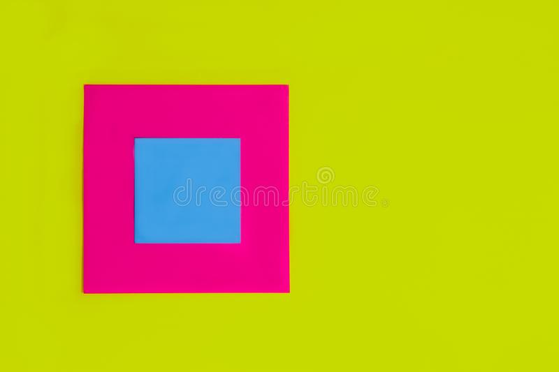 Blank square cyan blue reminder memo note for writing ideas, things to do on a pink fuchsia color square card and light green. Color paper background. Bright stock photos